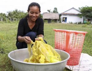Una mujer lava las bolsas de plástico recogidas en el pueblo camboyano de Chamcar Bei (Foto Efe)