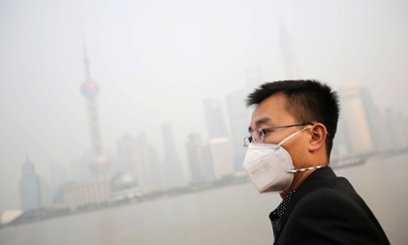 "A tourist with a protective mask watches the buildings at the Bund under heavy haze in Shanghai, China, Friday, Dec. 20, 2013. Shanghai's environmental protection bureau issued a ""yellow"" pollution warning this afternoon and said it was taking ""emergency emission reduction"" measures and recommends that children, the elderly and people suffering from heart disease or lung disease should stay indoors and cease outdoor exercises. (AP Photo/Eugene Hoshiko)"