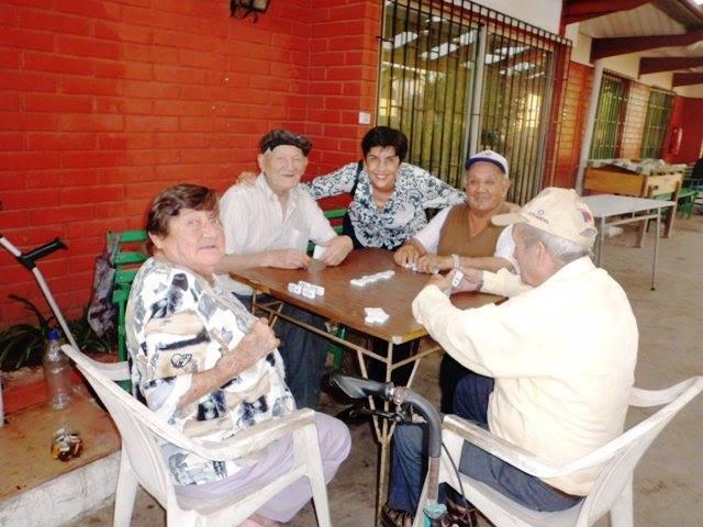Marisela Valero feliz rodeada de los jugadores de dominó en la Villa de Ancianos del Padre Hurtado, foto Marta Silva