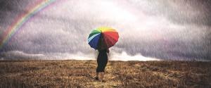 Una mujer con un paraguas camina bajo la lluvia en un campo, al fondo se ve un arco iris. Foto OMM