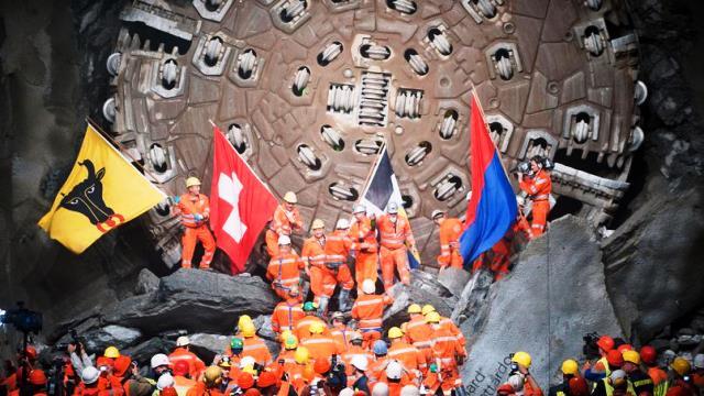 Obreros ondean las diferentes banderas de paises que atraviesa el tunel