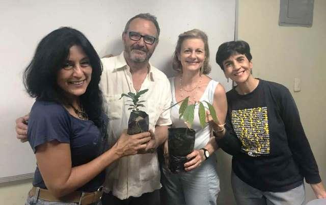 Enrique entrega a Zulma Bolívar, Helena Scannone y Marisela Valero especies de Café, cacao y cúrcuma para sembrarlas en la sede de la Asociación de Vecinos APRUCC